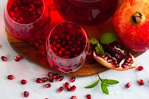 freshly prepared pomegranate juice in a decanter and two glasses