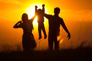 Silhouettes of a family of 3, who hold hands