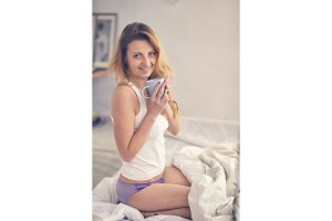 woman in the morning in a bed with a cup of coffee