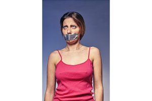 woman with his mouth glued with tape. Concept on humiliation and discrimination of women