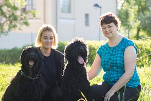 The girl and her mother and two black Russian Terrier sitting on the grass in the Park