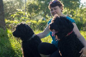 A woman and her two black Russian Terriers are on a walk in the Park