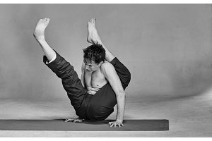 young man is engaged in yoga in a studio