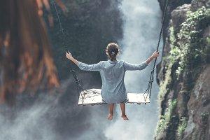 Beautiful woman swings near waterfall in the jungle of Bali island, Indonesia.