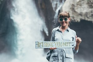 Young woman posing close to waterfall on Bali island.