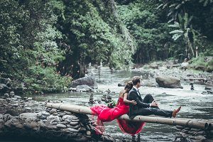 A beautiful young honeymoon couple posing on the river in the jungle of Bali island.