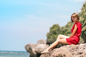 Girl in a red dress sitting barefoot on the stone close to sea shore. Tropical beach, Bali island. Sunny day.