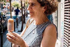 Elegant woman eating Ice cream on the street