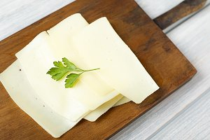 Slices of cheese on wooden board. Food