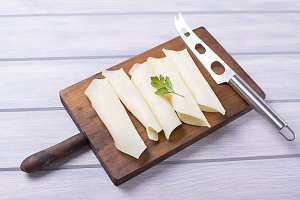 Slices of cheese rolled together with knife on wooden board. Food