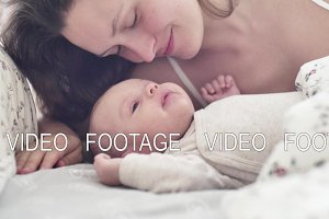 beautiful young mother smile and kiss her newborn child