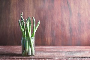Banches of fresh green asparagus in a jar on wooden background