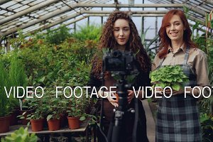 Cheerful female gardeners in aprons are talking and holding flowers while recording video for online blog about green plants using camera on tripod.