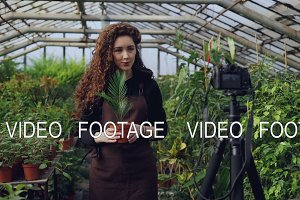 Young woman owner of hothouse is recording video about gardening for her videoblog standing in greenhouse and holding pot flowers. People and botany concept.