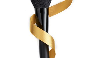 makeup brush and golden ribbon