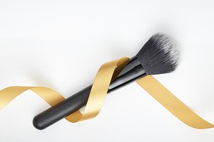 makeup brushes and golden ribbon