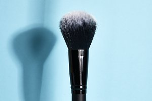 Make-up brush on Blue pastel background
