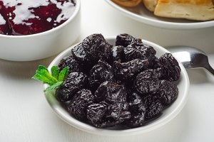 Prunes on small plate and plum jam.