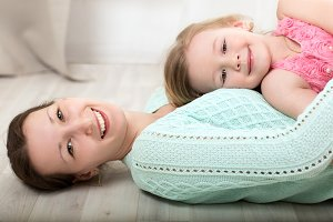 Smiling mother and daughter on floor
