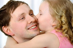 Little girl kissing fathers cheek