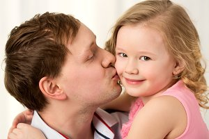 Daddy kissing beautiful little daugh