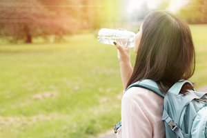 Woman drinking water outdoors in sunset in summer time