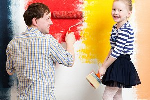 Happy girl painting wall with father