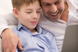 Happy dad and son with laptop