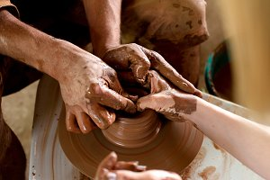 Mid-section of girls making pot in pottery workshop