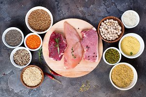 Raw food beef meat and chicken breast with cereals in bowl on stone dark background, flat lay