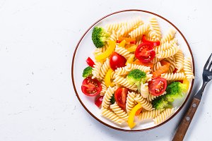 Vegan pasta fusilli with vegetables on white.