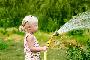 Little girl watering the grass in th