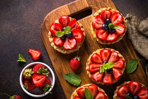Strawberry tart on dark table.