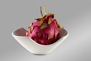 Whole dragon fruit in a white bowl against a grey background