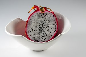 Dragon fruit cut in half in a white bowl against a grey background