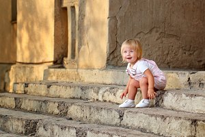 Girl sitting on steps of porch