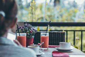 Young woman drinking a cup of coffee in the morning with the jungle view during luxury vacation in Bali island.
