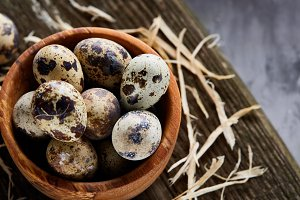 Wooden bowl filled with quail eggs on wooden board over white background, close-up, selective focus.