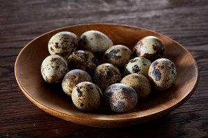 Fresh quail eggs in a wooden plate on a dark wooden background, top view, close-up