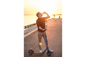 Young man drinking blue isotonic drink after riding on kick scooter in sunset sky background. Healthy lifestyle and fitness concept