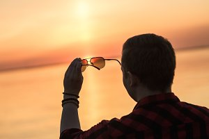 Sunset through sunglasses in male hands