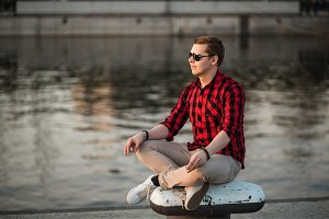 Guy sitting in the lotus position in city embankment and looking at the setting sun