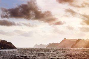 Rocky Atlantic shoreline under dramatic cloudscape. Sunrise on Cape Verde. View from the sea