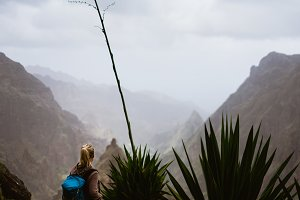 Female hiker in dusty mountain terrain enjoy spectacular view of sharp summits in the fog. Santo Antao Island Cape Verde