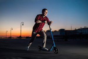 Young man rides a scooter by night street background.