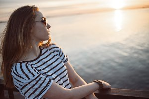 A young woman is looking at the sunset over a sea or river with beautiful soft sunny reflections in water