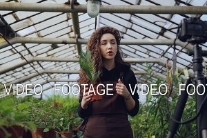 Pretty girl popular blogger is recording video about plants for her social media account with camera on tripod. Young woman is holding pot flower and talking.