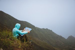 Traveler wear blue hoodie with the map sitting on the hill of a mountain in front of a gorgeous panorama view t othe valley