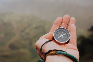 Starched palm with compass. Looking at the compass to figure out right direction. Foggy valley and mountains in background. Santo Antao. Cape Cabo Verde