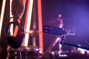 Studio microphone and headphones in the hand of a person close up, in a recording Studio or concert hall.